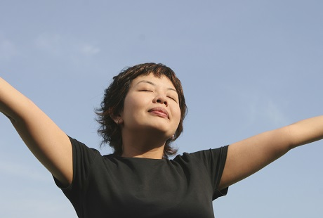 A women Praying with arms open behind a blue sky